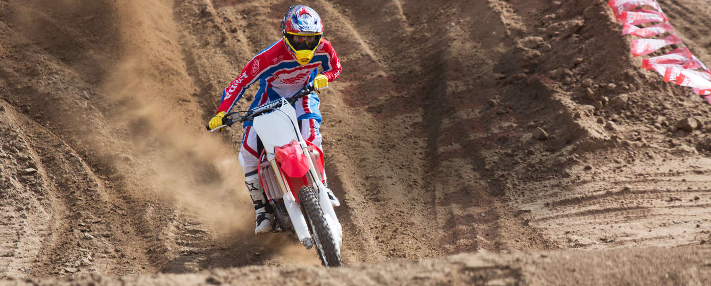 Front-facing CRF125R motorcycle with rider, on dirt track location.
